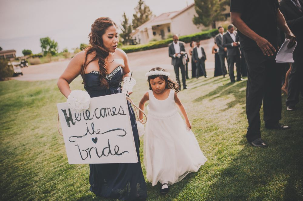san   diego wedding photographer | woman in dark blue strapless dress holding hand   of flower girl and holding 'here comes the bride' sign
