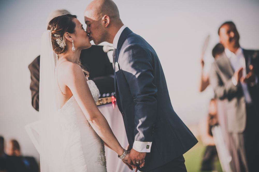 san   diego wedding photographer | bald groom in dark blue suit holding hands and   kissing bride with curly ponytail
