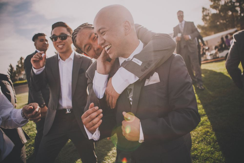 san   diego wedding photographer | man with fishtail braids hugging and touching   cheek of bald man smiling