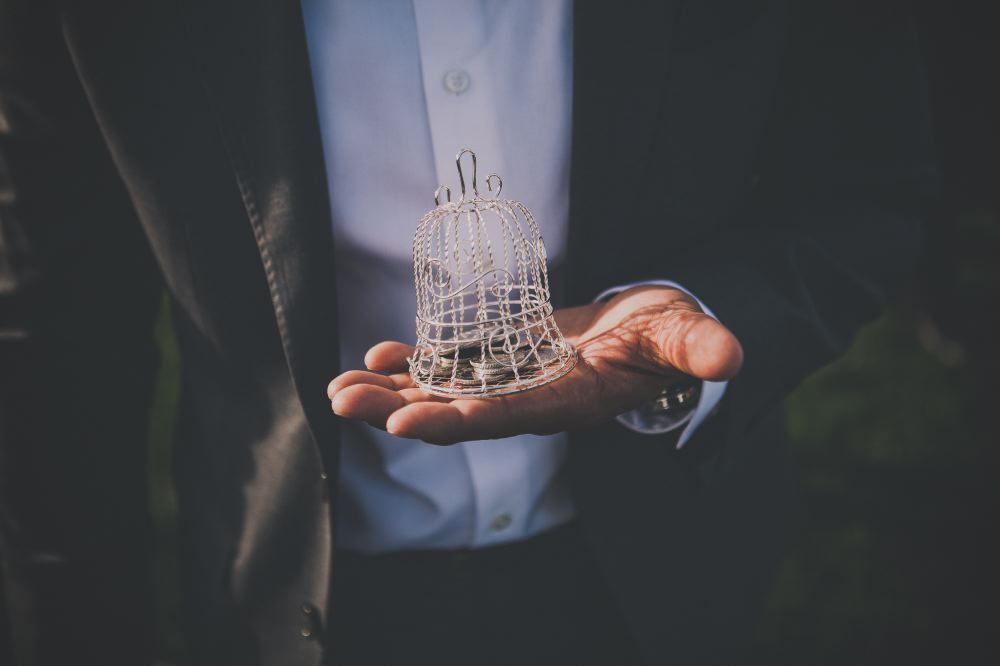 san   diego wedding photographer | neck-down shot of man with suit and watch   holding bell-shaped ornament