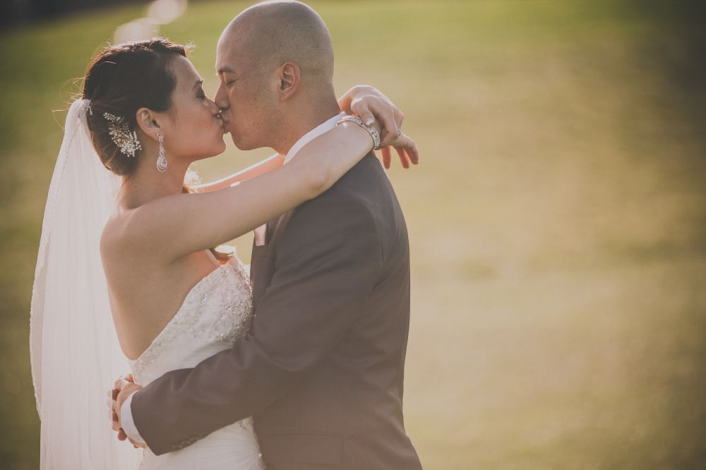 san   diego wedding photographer | bald groom in dark blue suit hugging bride's   waist and kissing bride with curly ponytail