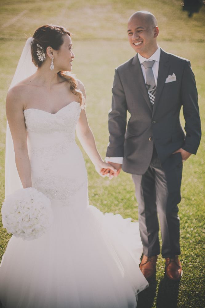 san   diego wedding photographer | bald groom in dark blue suit holding hand of   bride with curly ponytail and bride looking back at him