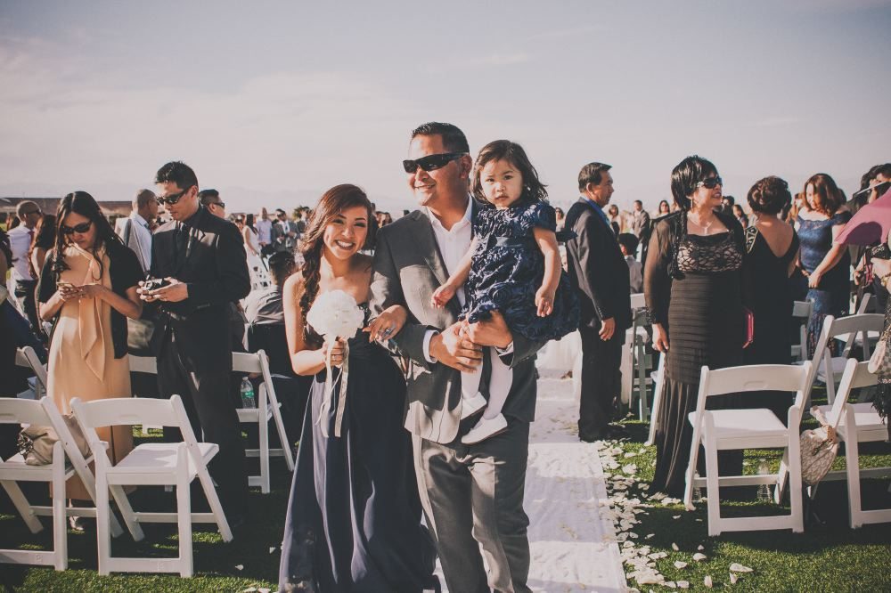san   diego wedding photographer | woman in blue strapless dress smiling at camera   with man in gray suit and sunglasses beside her carrying a child