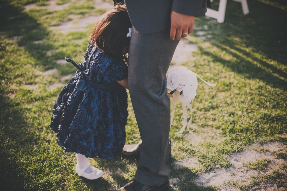 san   diego wedding photographer | child in blue dress holding a bouquet and   passing between man's legs
