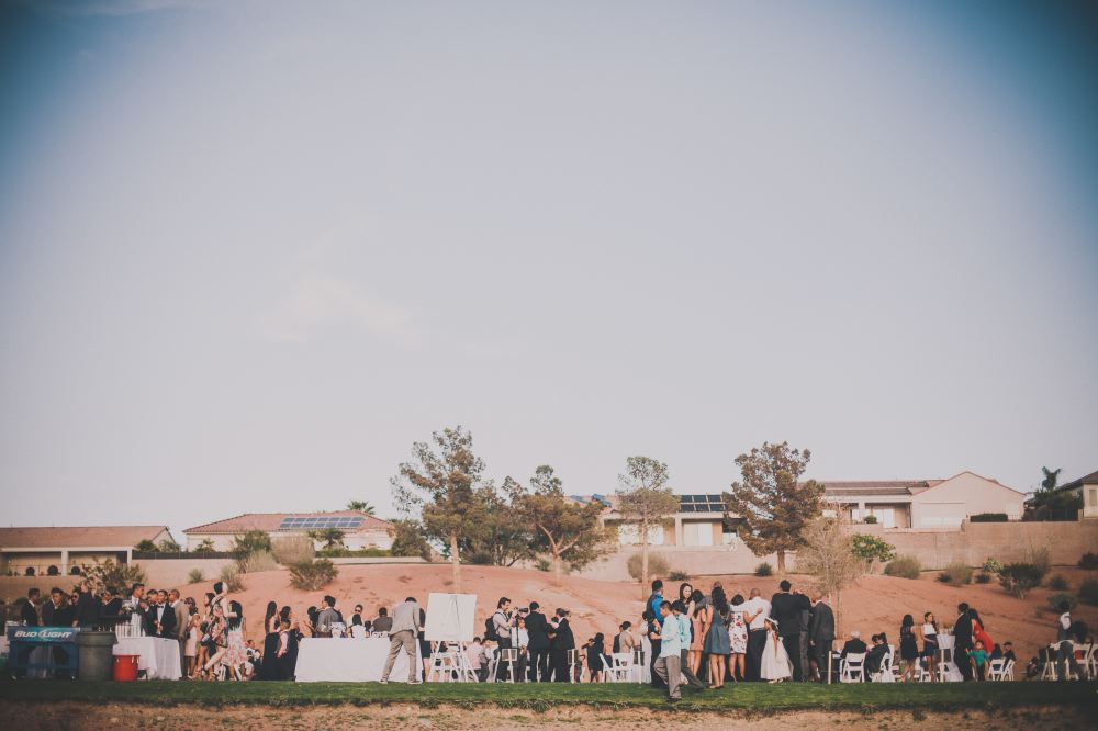 san   diego wedding photographer | far view of group of people standing below small   slope of land with trees and houses