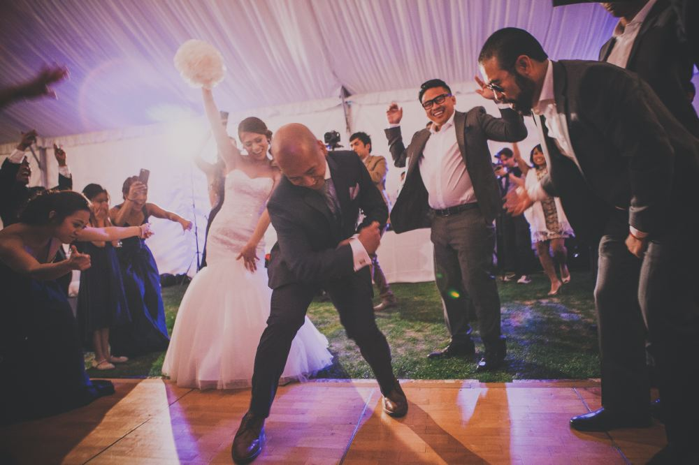san   diego wedding photographer | bald man with legs apart crouched forward and   dancing with bride behind him holding bouquet and dancing