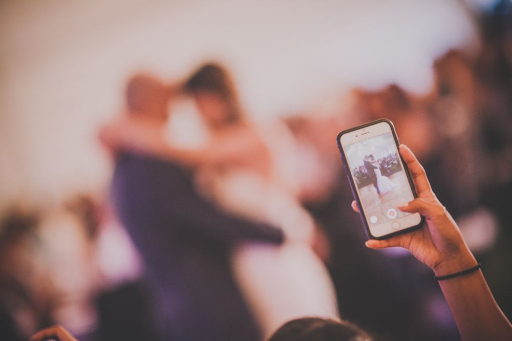 san   diego wedding photographer | woman holding up iphone taking photo of the   married couple dancing