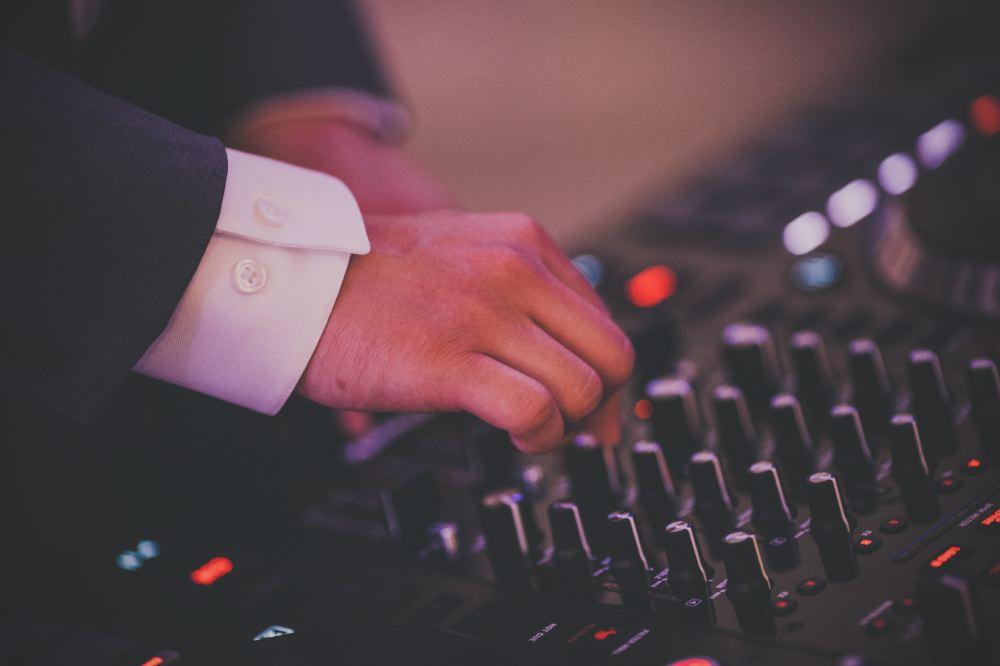 san   diego wedding photographer | man in dark blue suit adjusting audio system