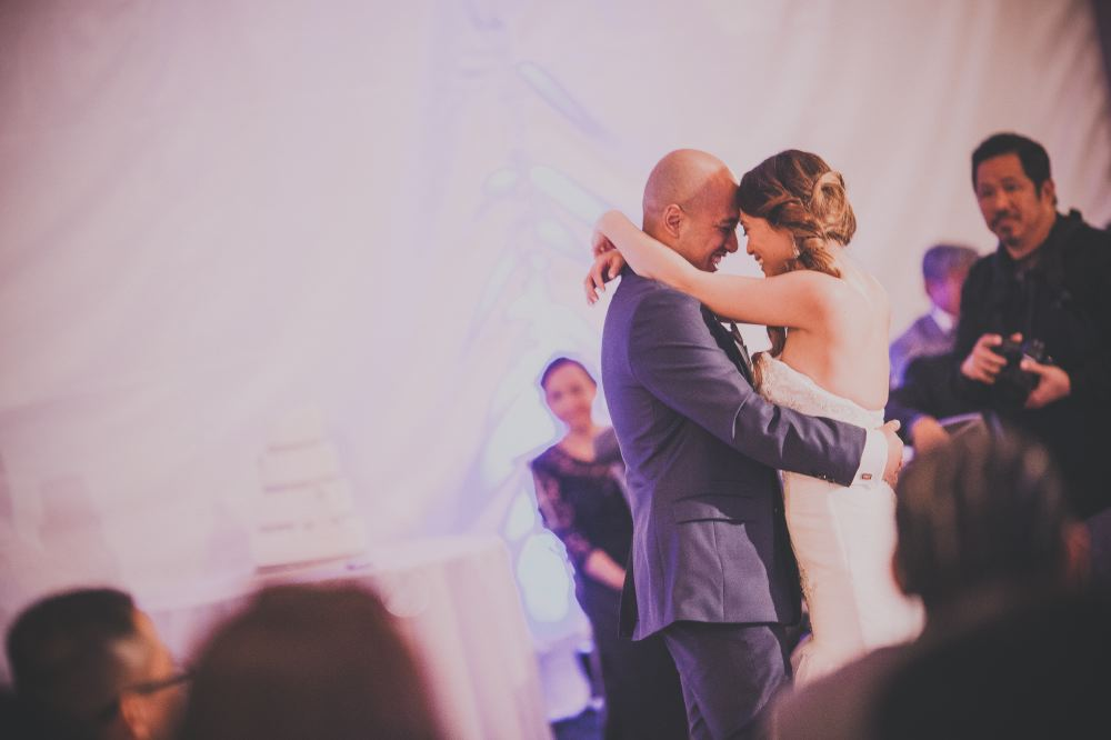 san   diego wedding photographer | bride with curly ponytail and bald groom   embracing and dancing against white backdrop