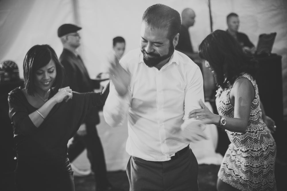 san   diego wedding photographer | monotone shot of man with full beard clapping   hands and dancing with two women