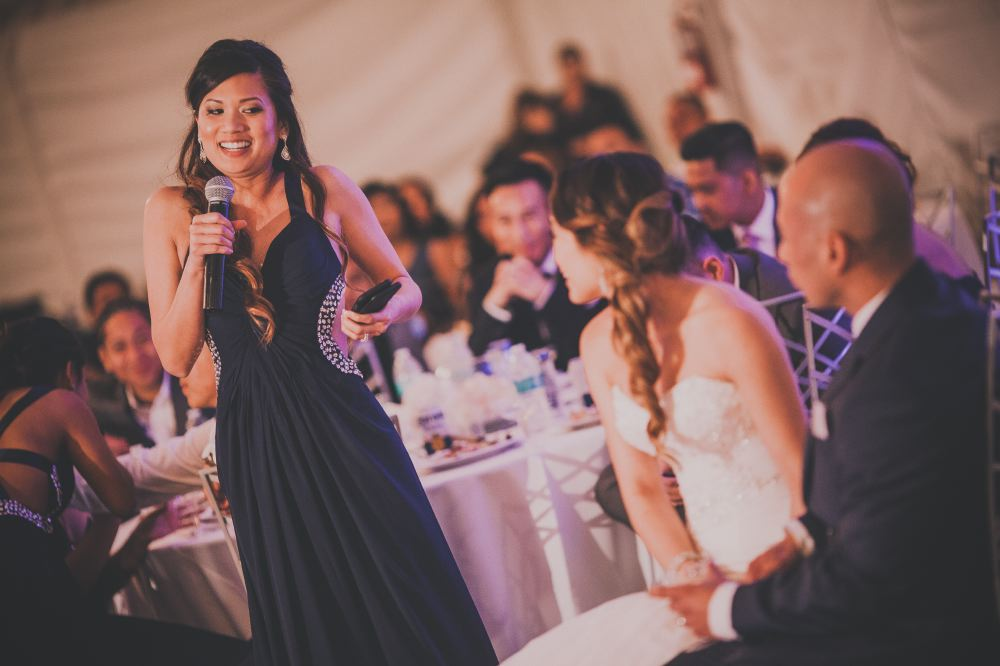 san   diego wedding photographer | woman with half-up hairdo and dark blue   sleeveless dress holding microphone and talking to married couple