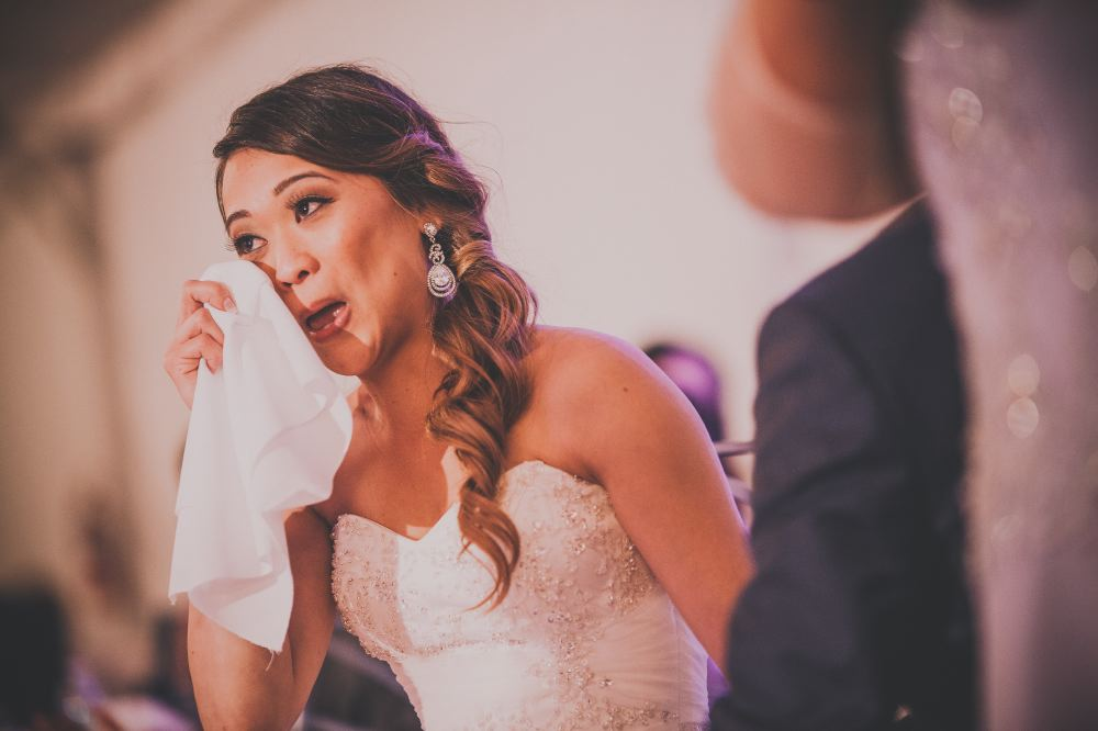 san   diego wedding photographer | bride with curly ponytail holding napkin to her   eyes to wipe tears