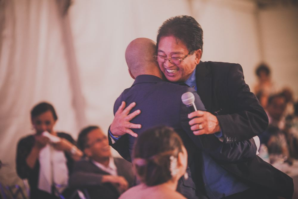 san   diego wedding photographer | man wearing glasses and blue polo holding   microphone and hugging bald man in dark blue suit