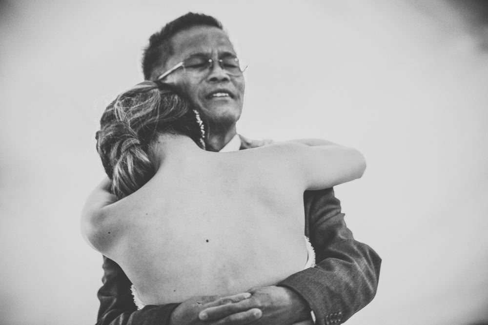san   diego wedding photographer | monotone shot of back of bride wearing backless   dress and hugging middle-aged man with glasses closing his eyes