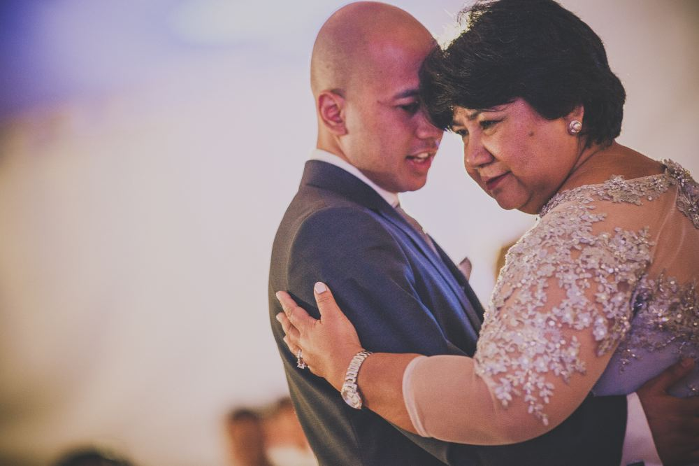 san   diego wedding photographer | bald man in suit dancing and talking with   middle-aged woman in long-sleeved gown