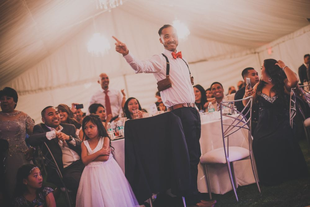 san   diego wedding photographer | man in suspenders and red bow tie standing and   pointing index finger up