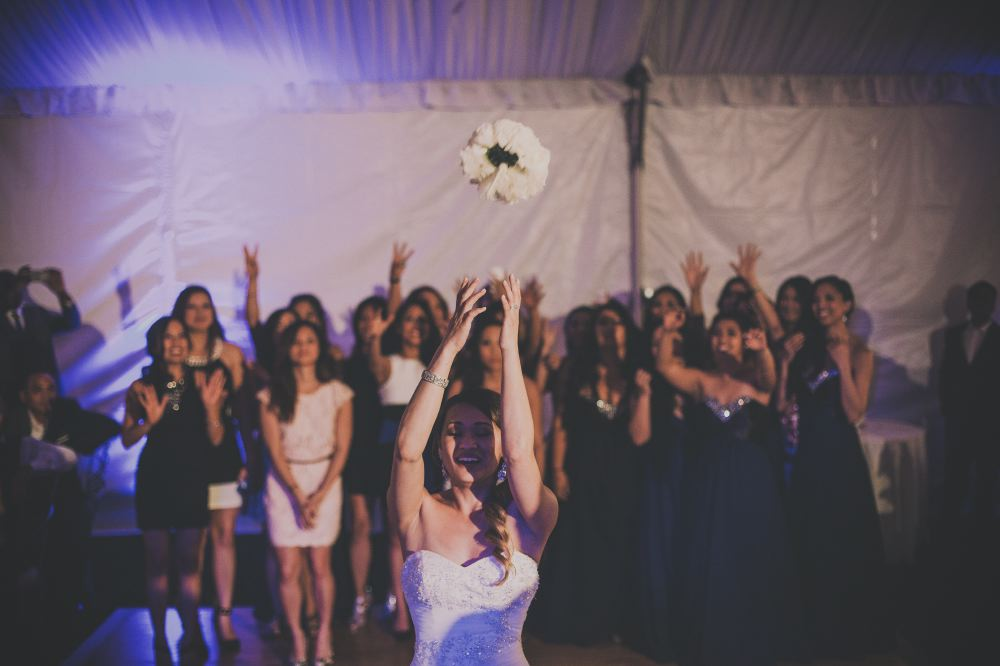 san   diego wedding photographer | bride with curly ponytail throwing white bouquet   to crowd of women wearing dark blue and white