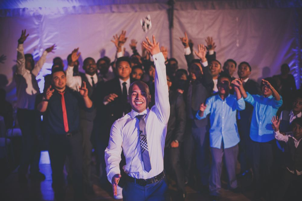 san   diego wedding photographer | bald man in checkered tie closing eyes and   throwing garter to crowd of boys and men