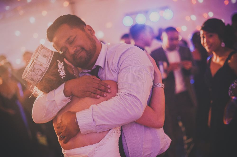 san   diego wedding photographer | man in long-sleeved polo and tie hugging bride   wearing crown made out of money