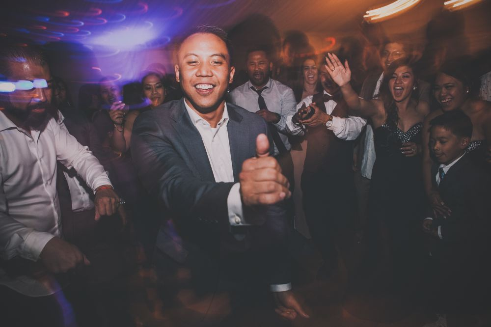 san   diego wedding photographer | man in dark blue suit making a thumbs up with   crowd surrounding him on dance floor with light distortion effect