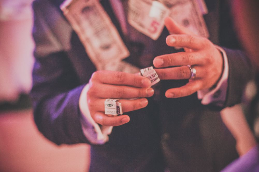 san   diego wedding photographer | man in suit with stapled money wearing rings   made out of money
