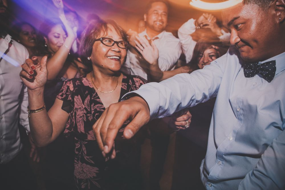 san   diego wedding photographer | woman with glasses and black floral dress   looking at man in blue polo and bowtie on dance floor with light distortion   effect