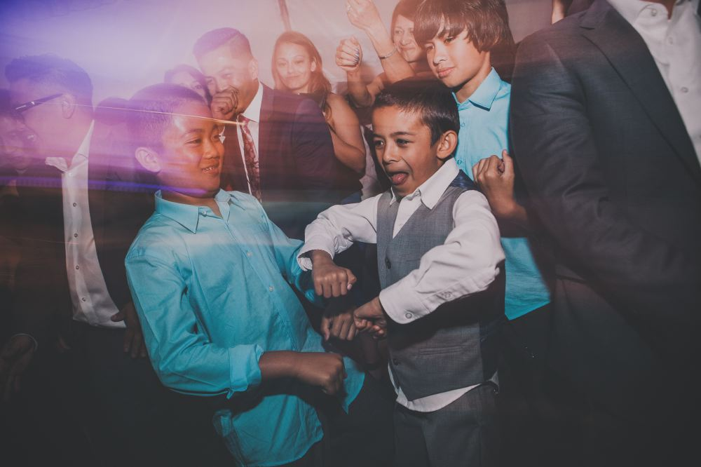 san   diego wedding photographer | boy in teal polo dancing with boy in white suit   and gray vest with light distortion effect