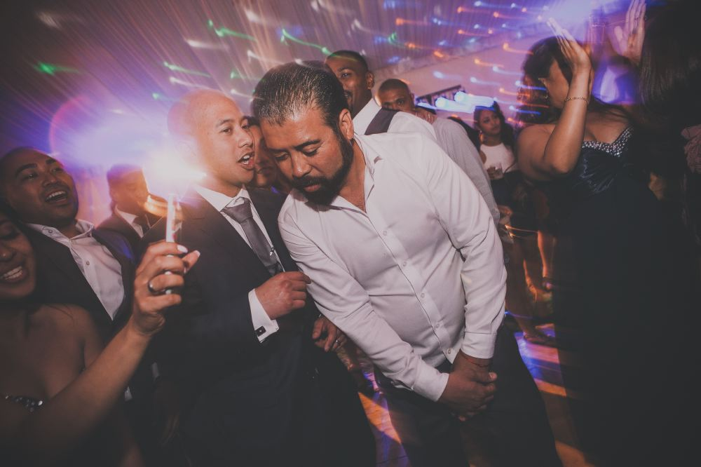 san   diego wedding photographer | bald man in blue suit whispering to man with   full beard and white polo on dance floor with light distortion effect