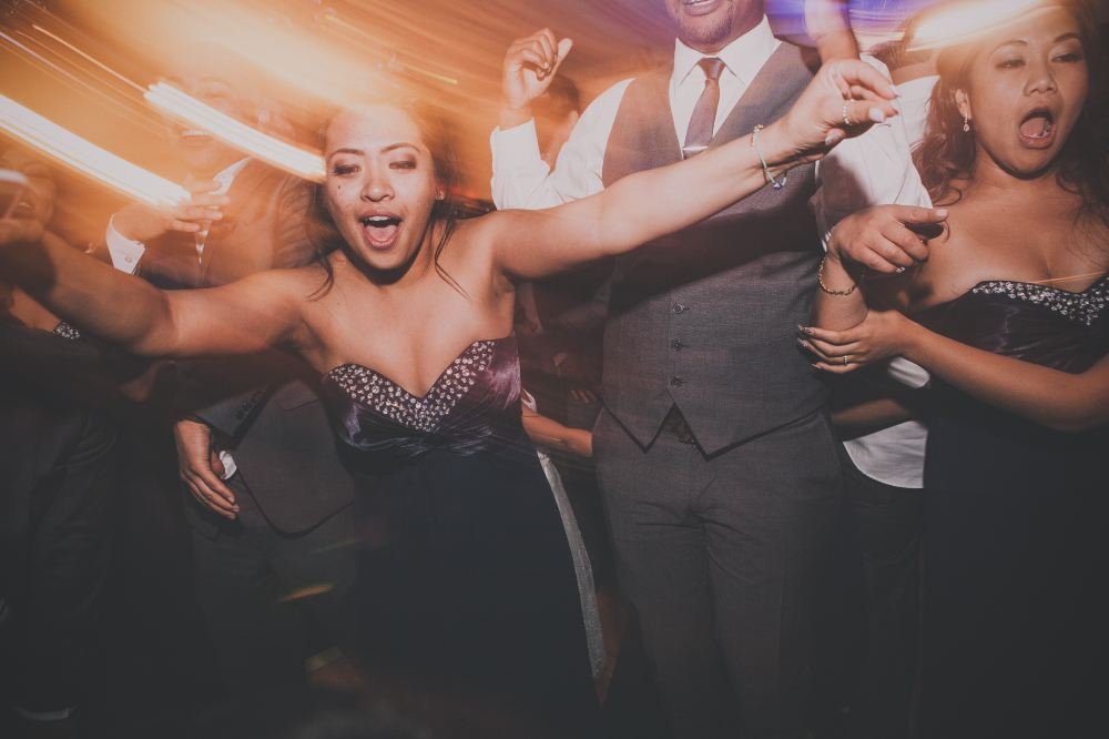 san   diego wedding photographer | women in dark blue strapless dresses screaming   and dancing on dance floor with light distortion effect