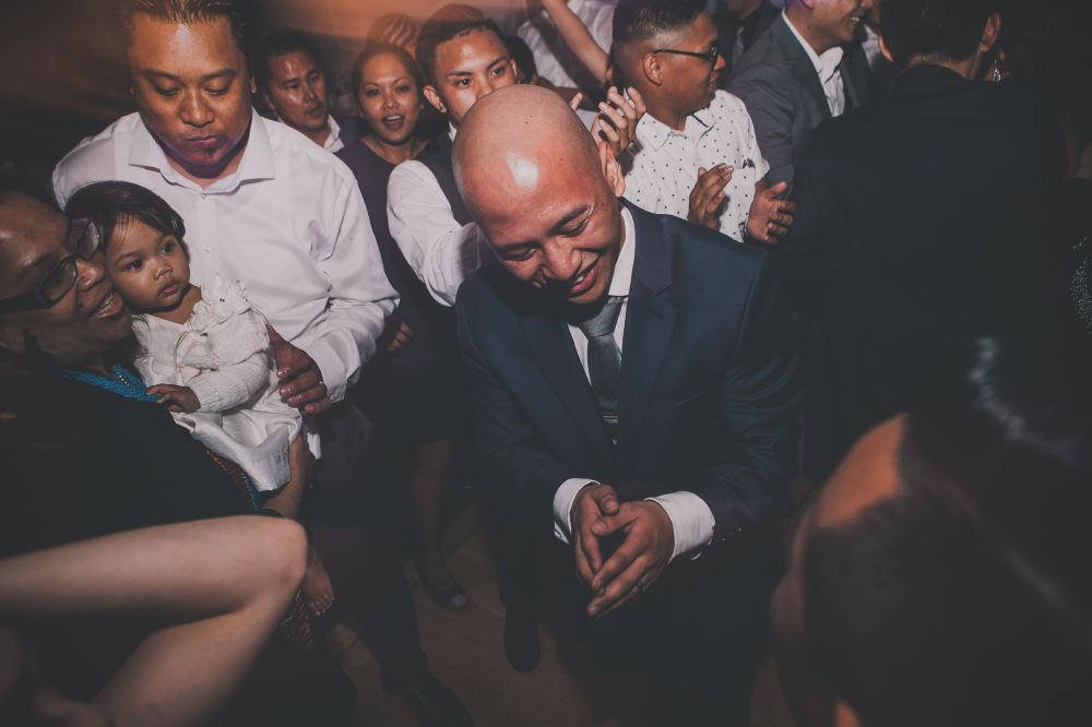 san   diego wedding photographer | bald man in blue suit with hands together and   surrounded by crowd on dance floor