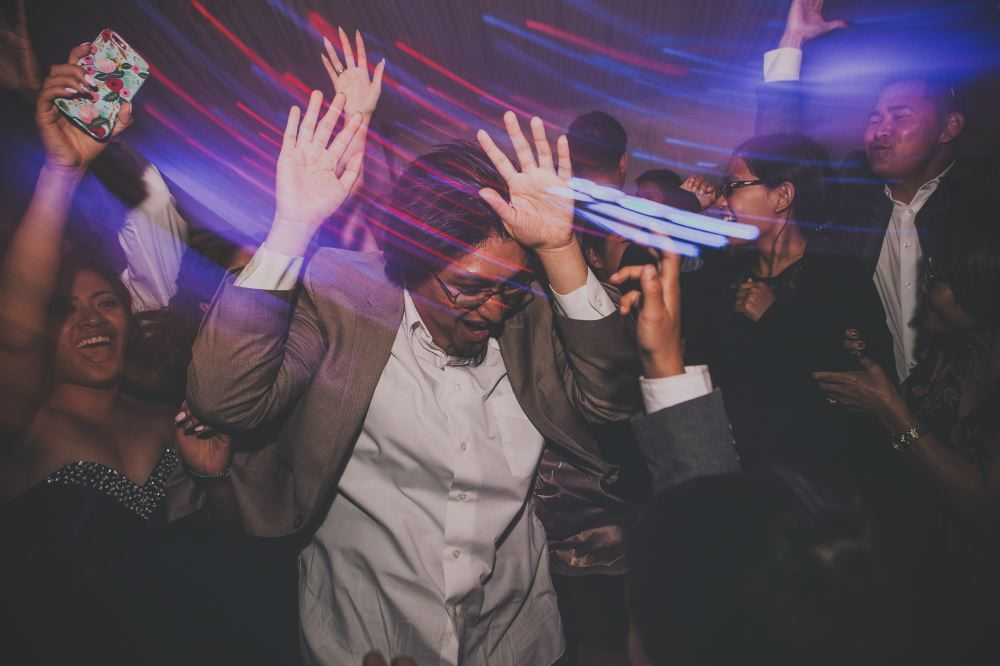 san   diego wedding photographer | man with glasses and beard raising hands on   dance floor with light distortion effect