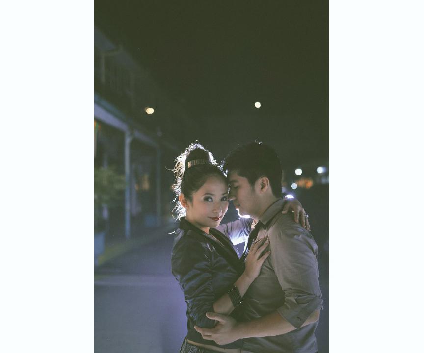 san   diego wedding photographer | man holding woman close on street illuminated by   light behind them