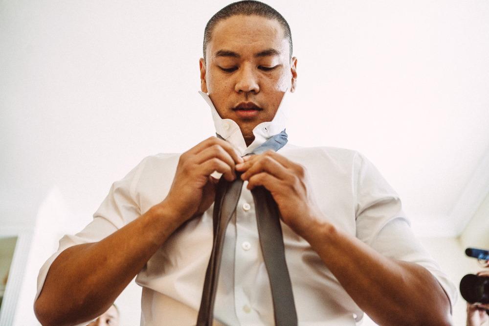 san   diego wedding photographer | man with short cut hair fixing his tie