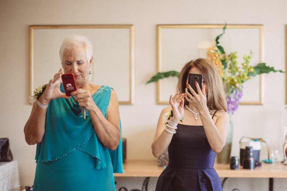 san   diego wedding photographer | middle aged woman in teal dress looking at phone