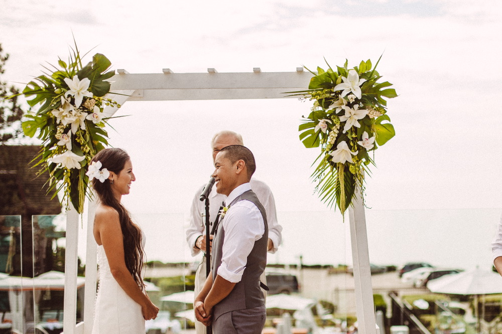 san   diego wedding photographer | bride in white dress and flowers in hair   standing in front of groom in grey vest