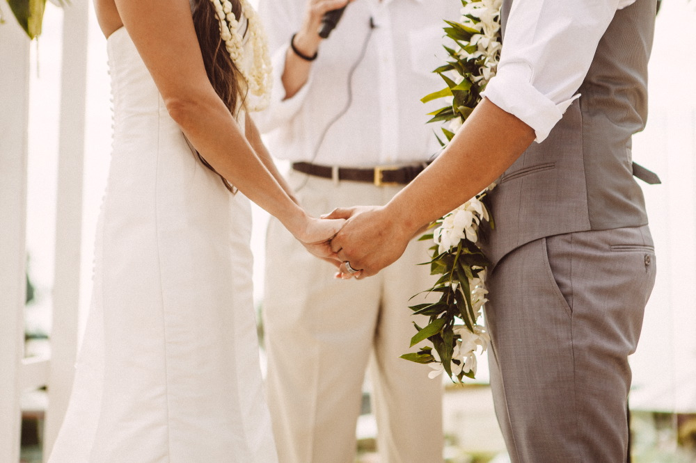 san   diego wedding photographer | lower body shot of couple holding hands in front   of officiator in white
