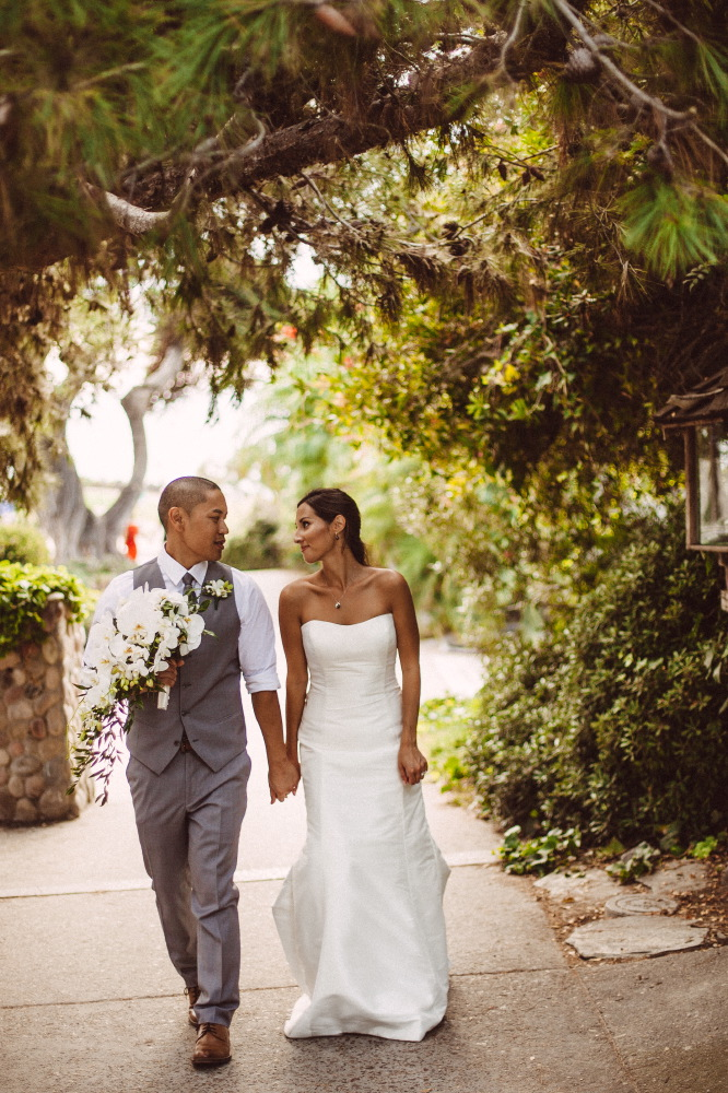 san   diego wedding photographer | groom in grey vest holding bouquet of white   flowers holding hands with bride