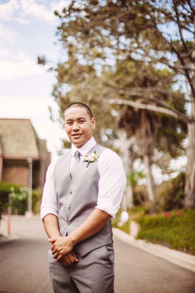 san   diego wedding photographer | groom in grey vest smiling with arms crossed in   front of him