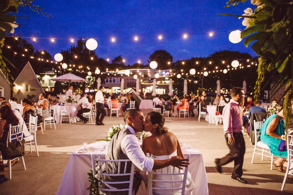 san   diego wedding photographer | bride and groom kissing sitting down with   wedding guests in background