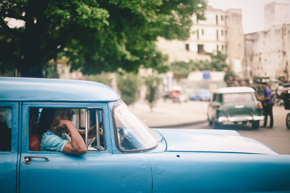 san diego wedding   photographer | woman in passenger seat of vibrant blue car with arm leaning   outside car window