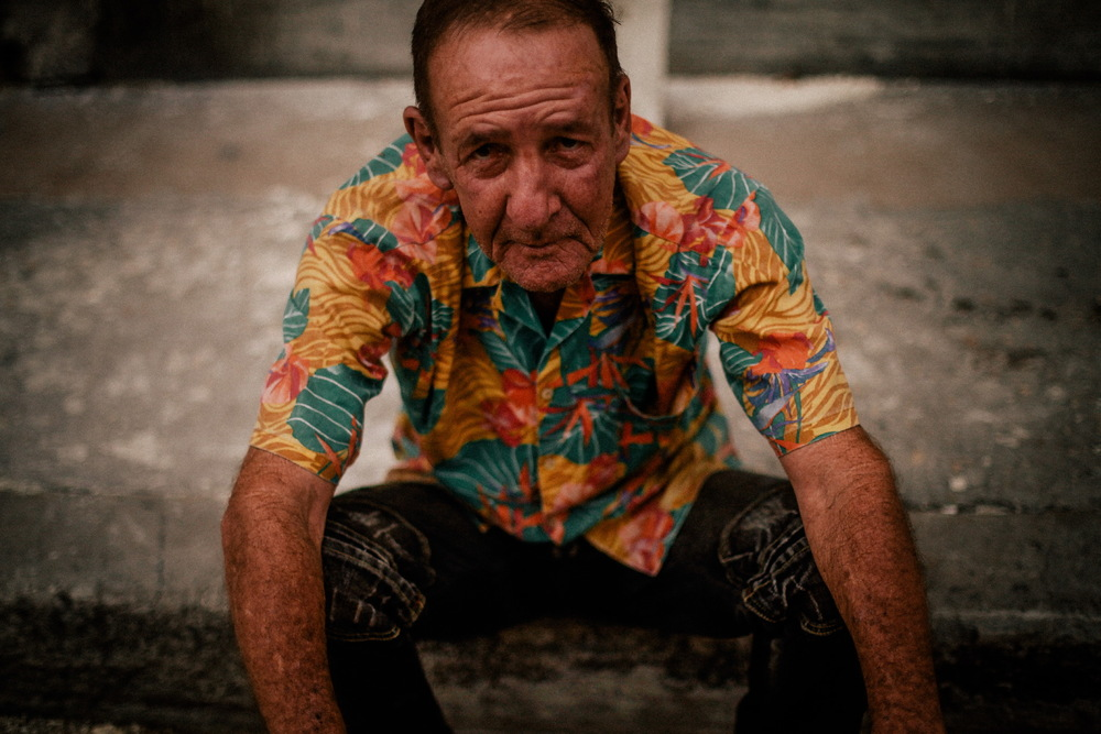 san diego wedding   photographer | man in floral hawaiian shirt sitting on curb