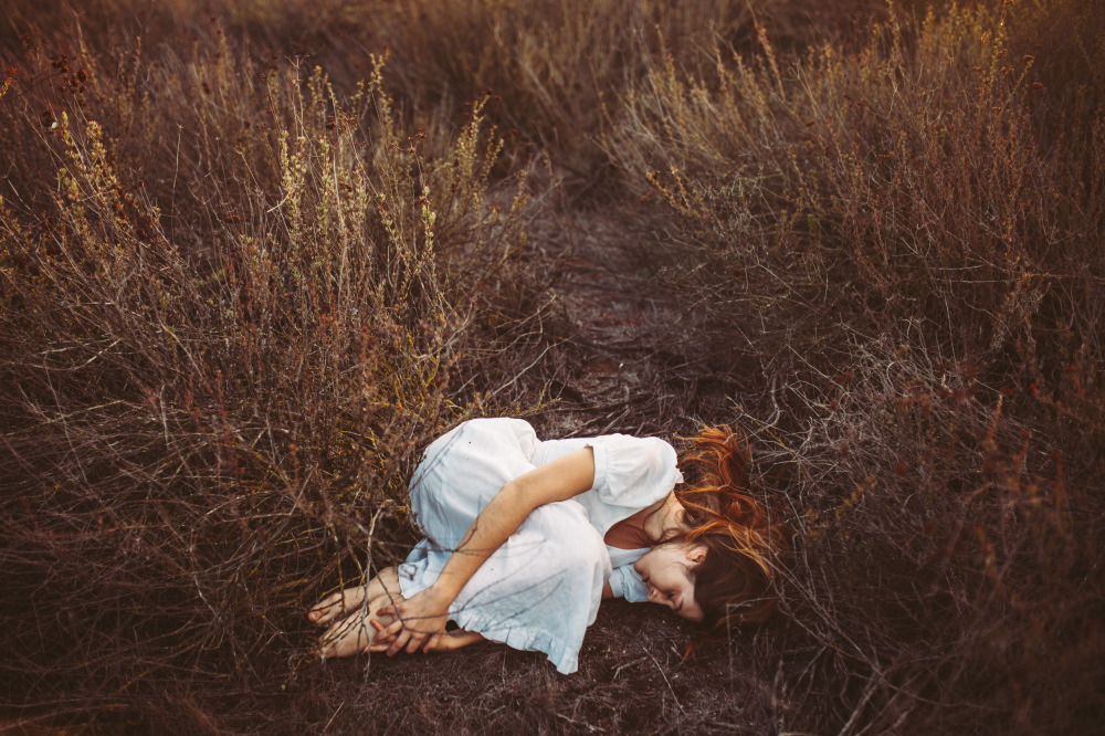 san diego wedding   photographer | long-haired brunette barefoot woman lying in fetal position on   field