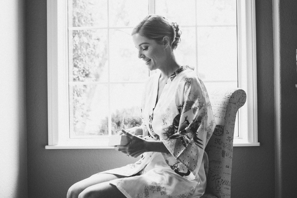 san diego wedding   photographer | monotone shot of woman in floral kimono sitting down smiling   looking down