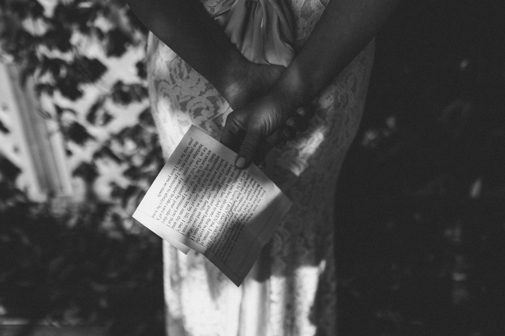 san diego wedding   photographer   monotone shot of woman holding paper behind her