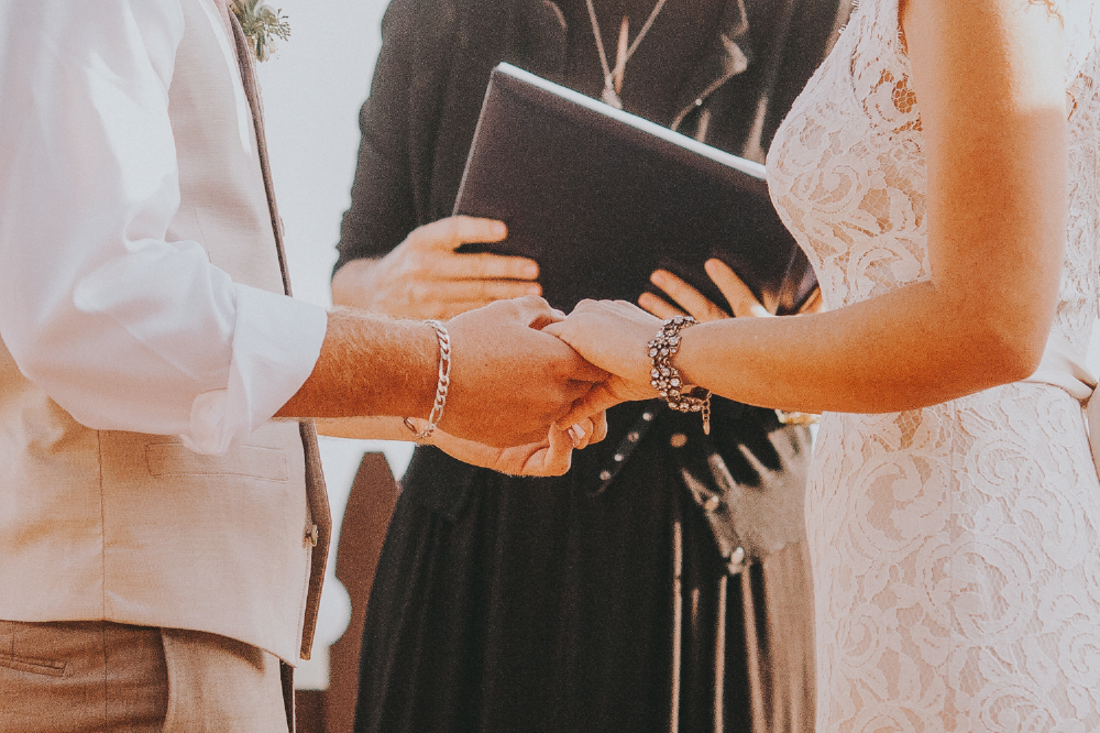 san diego wedding   photographer | closeup shot of groom holding bride's hand in front of   officiator holding book