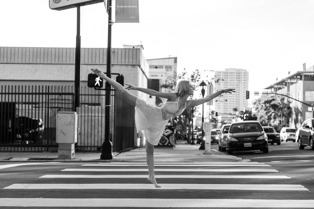 san diego wedding   photographer | monotone shot of barefoot blonde woman doing penche on   pedestrian lane
