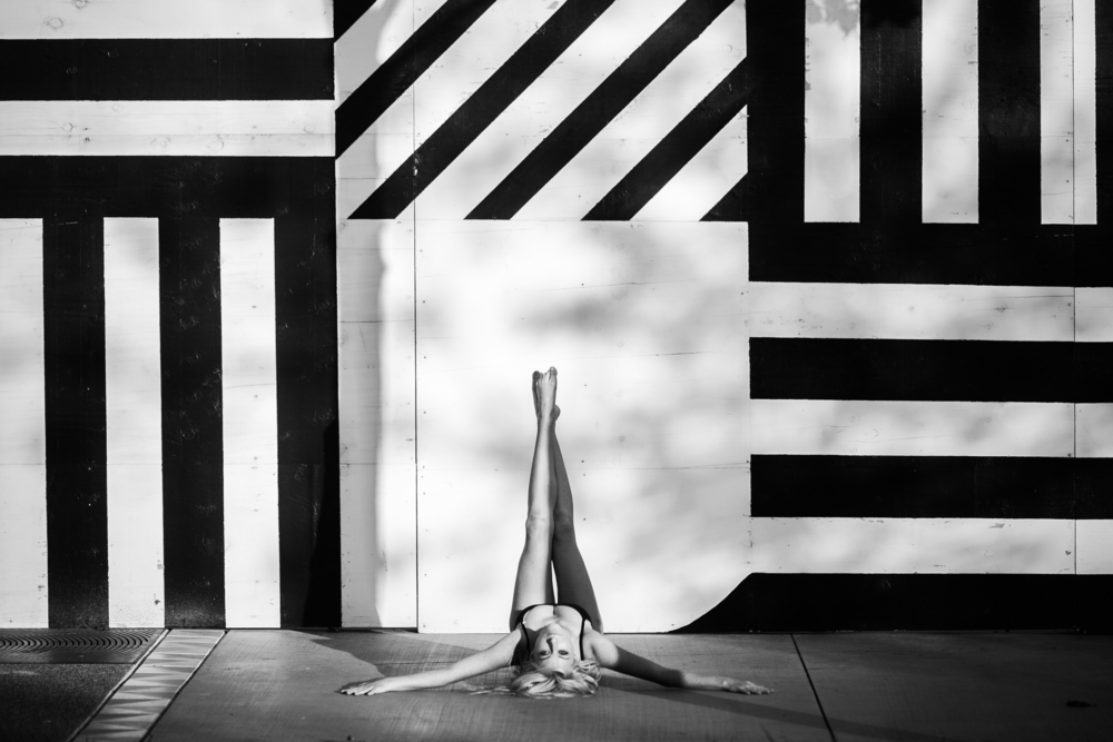 san diego wedding   photographer | monotone shot of barefoot blonde woman lying on ground with   legs crossed on wall