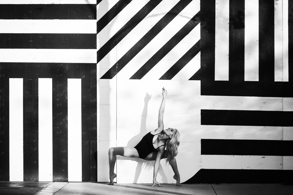 san diego wedding   photographer   monotone shot of barefoot blonde woman doing a plie squat with   one arm raised