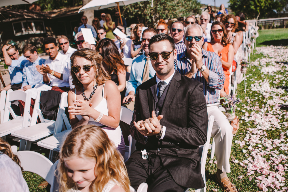san diego wedding   photographer | man in black suit and woman in white dress and shades in   forefront of applauding crowd
