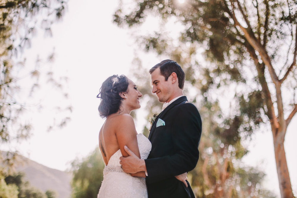 san diego wedding   photographer | low view shot of groom holding bride smiling with tree   branches in background